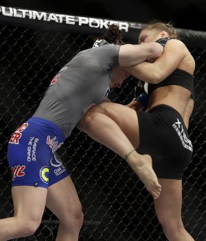 Ronda Rousey, right, knees Sara McMann during a UFC 170 mixed martial arts women's bantamweight title fight on Saturday, Feb. 22, 2014, in Las Vegas. Rousey won by TKO. (AP Photo/Isaac Brekken)