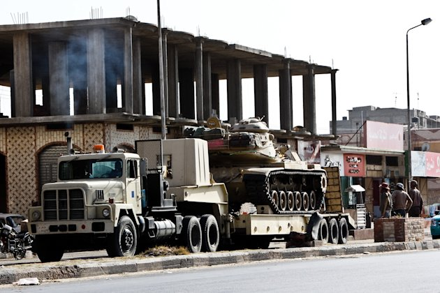 An Egyptian Army vehicle with a tank heads to the closed Rafah border crossing between Egypt and the Gaza strip, in Sheikh Zuweyid, northern Sinai, Egypt, Monday, May 20, 2013. Security officials said