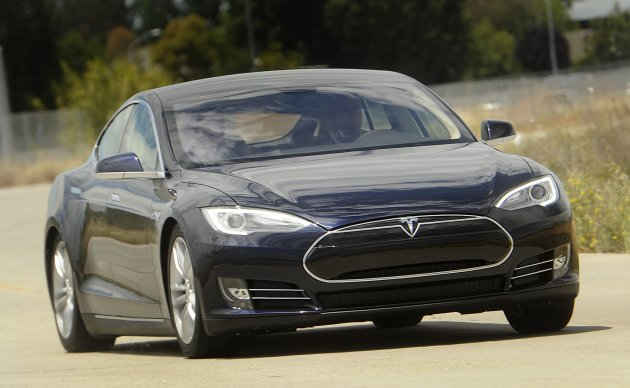 A Tesla Model S electric sedan is driven near the company's factory in Fremont