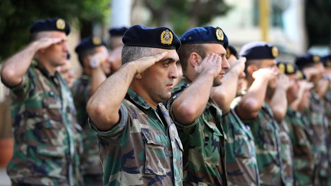 Lebanese army officers salute during the funeral procession for two soldiers killed Friday by a roadside bomb, during their funeral procession at the Lebanese army hospital, in Beirut, Lebanon, on Saturday, Sept. 20, 2014. Attackers blew up a roadside bomb near an army patrol near the Syrian border Friday, Sept. 19, 2014 killing two soldiers and wounding many in the latest spillover from the civil war next door, security official said. The violence appeared to be the latest in tensions between Lebanese troops and Syrian Islamic extremist rebels crossing the border in a spillover of Syria's civil war. (AP Photo/Hussein Malla)