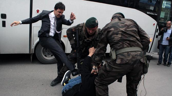 Yusuf Yerkel kicks a protester already held by police