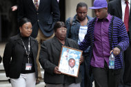 Edna Glover, second left, mother of Henry Glover, leaves Federal Court holding his photo, after the sentencing of two former New Orleans police oficers in his shooting death and burning of his body in New Orleans, Thursday, March 31, 2011. Former officer David Warren was sentenced to more than 25 years for shooting Glover without justification after Hurricane Katrina, and his ex-colleague Gregory McRae was given just over 17 years for burning the body. Right is Corey Glover, cousin of Henry, and background right is Patrice Glover, sister of Henry.
