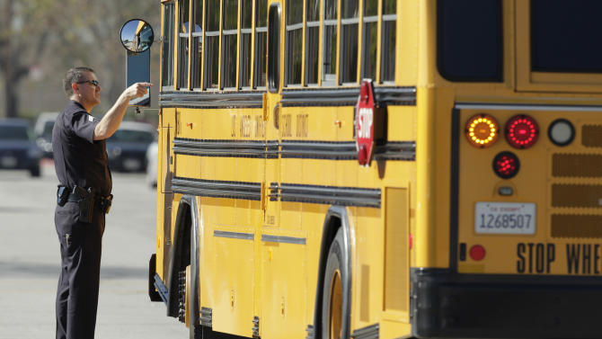 A police officer talks to a school bus driver as the bus arrives to pick up students at Gardena High School in Gardena, Calif., Tuesday, Jan. 18, 2011, after reports of a number of students being wounded during a shooting.  (AP Photo/Jae C. Hong)