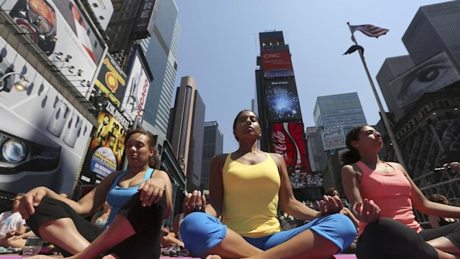 """People practice yoga in New York's Times Square, Friday, June 21, 2013. Yoga enthusiasts marked the longest day of the year with five free """"Mind Over Madness"""" yoga classes in Times Square. (AP Photo/Mary Altaffer)"""