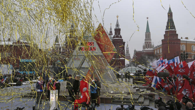 Confetti hovers in the air, as a crowd of sports enthusiasts waving Russian and Moscow flags  surrounds  the one-year count down clock for the upcoming 2014 Sochi Olympics during  the launching ceremony in Moscow, Russia, Thursday, Feb. 7, 2013. The Kremlin, right, and State Historic Museum are at the background.(AP Photo/Mikhail Metzel)