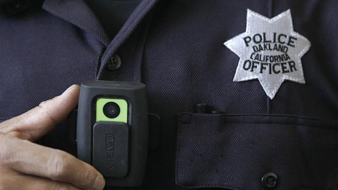 In this June 16, 2011 file photo, Oakland Police officer Huy Nguyen shows a video camera worn by some officers in Oakland, Calif. A judge who slammed New York City's stop-and-frisk program as discriminatory has suggested a pilot program in which officers wear cameras on their uniforms to record street encounters. (AP Photo/Jeff Chiu, file)