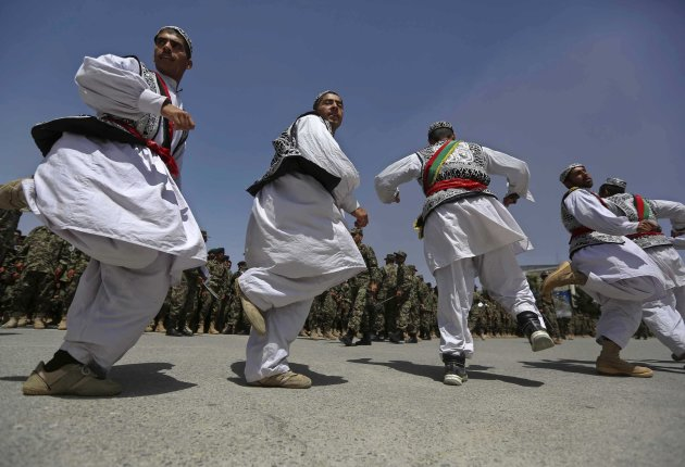 Newly graduated Afghan National Army soldiers, dressed in traditional clothes, dance during their graduation ceremony in Kabul