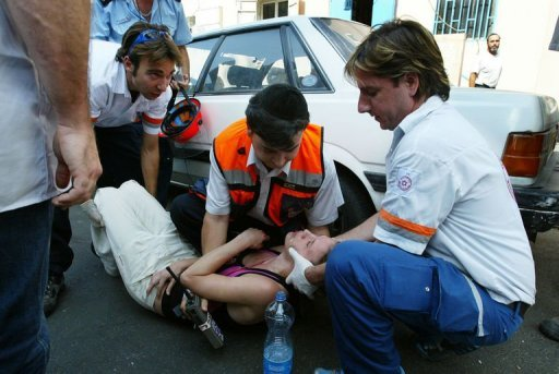 Israeli emergency workers help a woman who had an epileptic fit in Tel Aviv on November 1, 2004. A tiny device implanted in the brain of epilepsy sufferers has for the fist time been able to predict the onset of seizures, scientists reported on Thursday