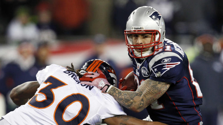 New England Patriots tight end Aaron Hernandez, right, evades a tackle by Denver Broncos free safety David Bruton (30) during the first half of an NFL divisional playoff football game Saturday, Jan. 14, 2012, in Foxborough, Mass. (AP Photo/Elise Amendola)