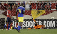 A ball headed by Ecuador forward Jaime Ayovi, not pictured, goes into the goal past the diving attempt of U.S. goalkeeper Tim Howard, right, in the second half of an international soccer friendly game, Tuesday, Oct. 11, 2011, in Harrison, N.J. (AP Photo/Julio Cortez)