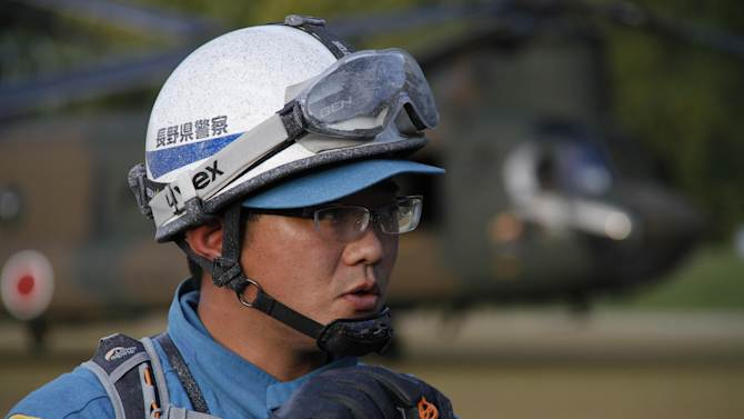 A Nagano Prefectural police officer covered by volcanic ash talks to the media after coming back from his mission to recover bodies still near the summit as Mount Ontake continues to erupt in Otaki in Nagano Prefecture, central Japan, Wednesday, Oct. 1, 2014. Police who recovered a dozen bodies on Wednesday portrayed a painful scene of death around the summit where hikers enjoying a weekend autumn hike were caught by the mountain's surprise eruption. (AP Photo/Koji Ueda)