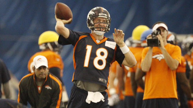 Denver Broncos quarterback Peyton Manning (18) takes part in drills in an indoor facility after inclement weather forced the cancellation of an outdoor session at NFL football training camp in Englewood, Colo., Friday, July 27, 2012. (AP Photo/David Zalubowski)