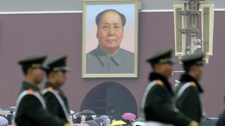 Chinese paramilitary policemen march near a portrait of late Chinese leader Mao Zedong on the Tiananmen Square in Beijing Saturday, Nov. 10, 2012. (AP Photo/Lee Jin-man)