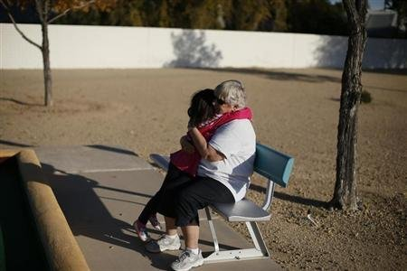 A child and a senior citizen embrace in Sun City