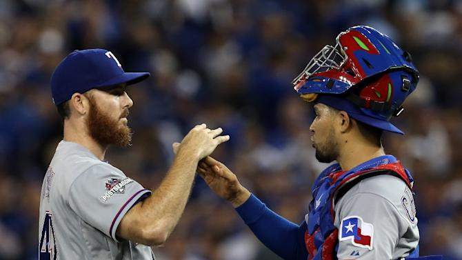 Sam Dyson of the Texas Rangers celebrates with teammate Robinson Chirinos after victory against the Toronto Blue Jays in Toronto on October 8, 2015