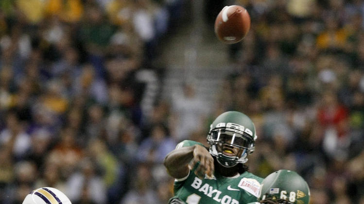 Baylor quarterback Robert Griffin III, rear, throws a pass during the first half of the Alamo Bowl college football game against Washington, Thursday, Dec. 29, 2011, at the Alamodome in San Antonio. (AP Photo/Darren Abate)
