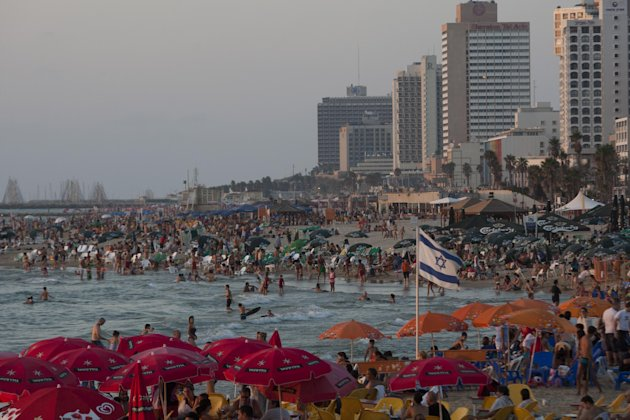In this picture taken on Friday, Aug. 10, 2012 , people enjoy the Mediterranean Sea in Tel Aviv, Israel. Israel is facing a possible showdown with Iran over its suspect nuclear program, worrying about neighboring Syria's bloody civil war spilling across the border and dealing with armed militants trying to infiltrate from Egypt's lawless Sinai Peninsula. But that doesn't seem to be deterring hundreds of thousands of tourists from flocking to Israel each month. Despite the region's turmoil, Israel is enjoying an unexpected tourism boom, and 2012 is shaping up to be a record year. (AP Photo/Ariel Schalit)