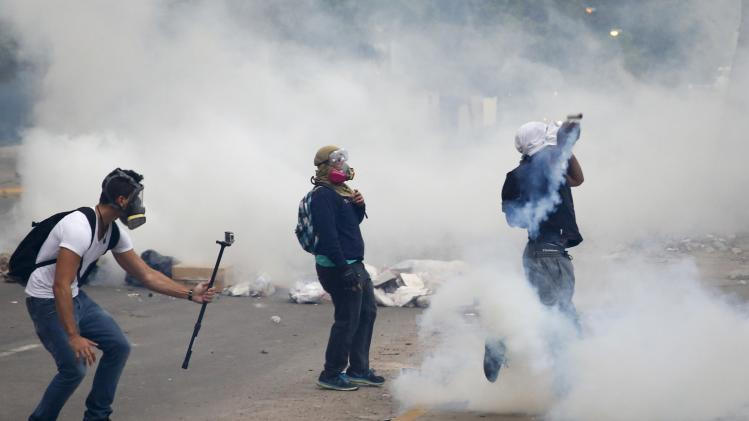 An anti-government protester films another protester throwing a gas canister back at police during a protest against President Nicolas Maduro's government in Caracas