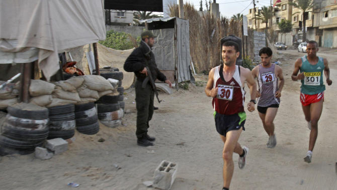 FILE - In this Thursday, May 5, 2011 file photo, Palestinian Omar Abu Said, left, Azmi Majaideh, center, and  Husam Naseir, right, participate in the first Gaza marathon as they run past a Hamas security officer manning a checkpoint in Beit Lahiya, northern Gaza Strip, on  Tuesday, March 5, 2013,  A U.N aid agency canceled the Gaza marathon on Tuesday, March 5, 2013 after the Palestinian territory's militant Hamas rulers banned women from participating in the annual sporting event.  (AP Photo/Adel Hana, File)