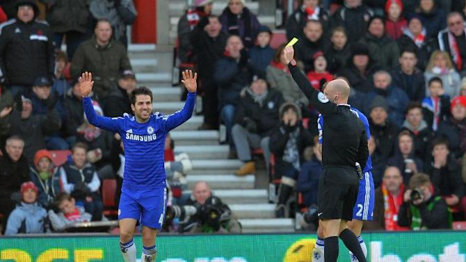 Chelsea's Cesc Fabregas (L) reacts as referee Anthony Taylor shows him a yellow card for simulation after Febregas went down in the Southampton penalty area during the Premier League match at St Mary's Stadium on December 28, 2014