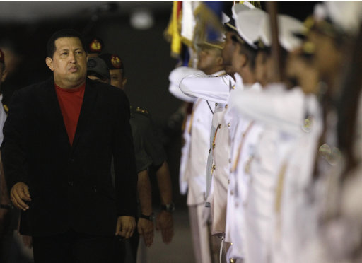 Venezuela's President Hugo Chavez reviews the troops upon his arrival at the Simon Bolivar airport in Maiquetia , Venezuela, Friday March 16, 2012. Chavez returned home Friday nearly three weeks after undergoing cancer surgery in Cuba.