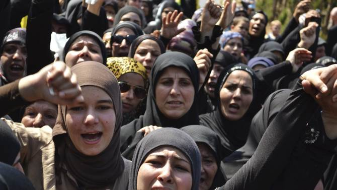 Lebanese Shi'ite Muslim women chant slogans as they mourn the death of a Hezbollah fighter who was killed in Syria, during his funeral in al-Mansouri town