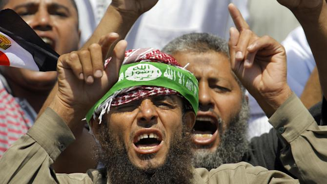 "Supporters of Egypt's Islamist President Mohammed Morsi shout anti-opposition slogans at a public square outside the Rabia el-Adawiya Mosque in Cairo, not far from the presidential palace, during a rally in Cairo, Saturday, June 29, 2013. Arabic on the headband reads, ""there is no God but Allah and Muhammad is the Messenger of Allah."" Thousands of supporters and opponents of Egypt's embattled Islamist president are holding rival sit-ins on the eve of what are expected to be massive opposition-led protests aimed at forcing Mohammed Morsi's ouster. The demonstrations early Saturday follow days of deadly clashes in a string of cities across the country that left at least seven people dead, including an American, and hundreds injured. (AP Photo/Amr Nabil)"