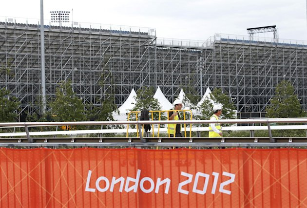 Workers carry scaffolding next to the Riverbank Arena in the Olympic Park in the 2012 Summer Olympics, Sunday, July 15, 2012, in London. The Riverbank Arena will be the hockey competition venue during the Olympics. (AP Photo/Jae Hong)