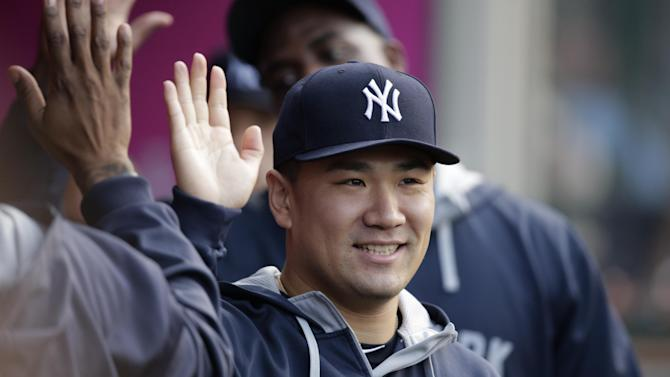 New York Yankees starting pitcher Masahiro Tanaka, of Japan, high-fives teammates in the dugout before a baseball game against the Los Angeles Angels, Tuesday, June 30, 2015, in Anaheim, Calif. (AP Photo/Jae C. Hong)