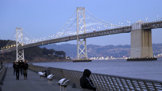 A man sits bundled up as he gets a view of the San Francisco Oakland Bay Bridge on Thursday, Dec. 5, 2013, in San Francisco. Parts of the U.S. are getting a blast of wintry weather, some experiancing frigid temperatures. (AP Photo/Marcio Jose Sanchez)