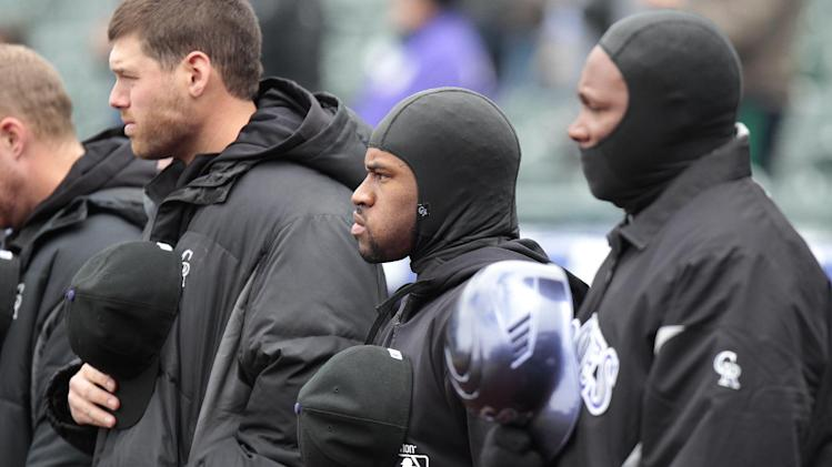 File-This April 23, 2013 file photo shows Colorado Rockies' Eric Young Jr., center, and others trying to keep warm in below-freezing weather before the first baseball game of a doubleheader against the Atlanta Braves in Denver. When the Atlanta Braves and Colorado Rockies started up at Coors Field in late April, it was 23 degrees. That made it the coldest game time temperature since STATS began recording them more than two decades ago. (AP Photo/Barry Gutierrez, File)