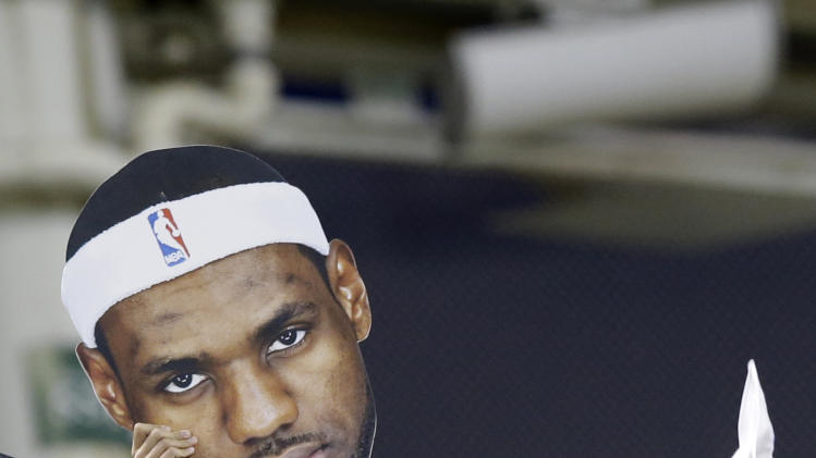 A fan holds up a LeBron James poster at the Cleveland Indians vs New York Yankees baseball game Thursday, July 10, 2014, in Cleveland. Long-suffering Cleveland sports fans are anticipating an announcement on the possible return of four-time NBA MVP LeBron James to the Cavaliers. (AP Photo/Tony Dejak)