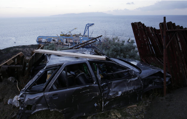 The Costa Concordia cruise ship leans on its side of the Tuscan Island Isola del Giglio, Italy, Saturday, Jan. 12, 2013. More time and money will be needed to remove the Costa Concordia cruise ship fr