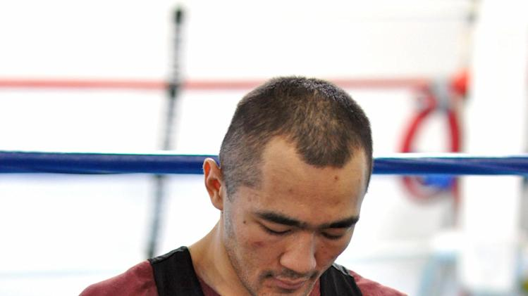 In this photo taken April 5, 2014, WBA and IBA light heavyweight boxing champion Beibut Shumenov, of Kazakhstan, tapes his hands for a workout in Las Vegas. Shumenov and IBF light heavyweight champion Bernard Hopkins will fight at the DC Armory on Saturday, April 19. (AP Photo/Joe Coomber)