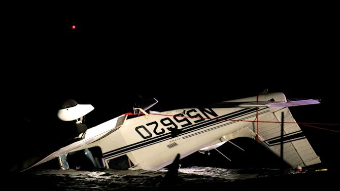 A small plane sits upside down on the bank of Creve Coeur Lake in Maryland Heights, Mo., on Wednesday, Oct. 24, 2012.  The pilot is identified as 78-year-old Russell Hazelton of Factoryville, Pa., was killed and his wife, 69-year-old Suzanne Hazelton, is in critical condition.  (AP Photo/St. Louis Post-Dispatch, Christian Gooden)