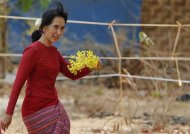 Aung San Suu Kyi carries flowers as she visits a polling station in Kawhmu township