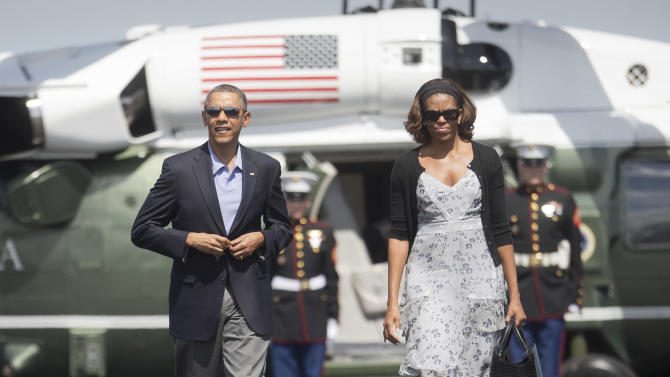 President Barack Obama and first lady Michelle Obama walk across the tarmac before their departure on Air Force One at Homestead Air Reserve Base, Sunday, March 9, 2014, in Homestead, Fla. Obama returned to Washington after spending the weekend in Florida. (AP Photo/Pablo Martinez Monsivais)