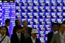 Pedestrians walk past a share prices board in Tokyo, where the Nikkei 225 index fell 0.37 percent, or 56.81 points to 15,138.96