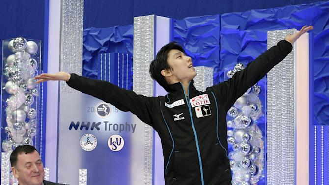 Yuzuru Hanyu of Japan, flanked by his coach Brian Orser of Canada, celebrates to win after performing the men's singles free skating program at the ISU Grand Prix of Figure Skating in Nagano, Japan