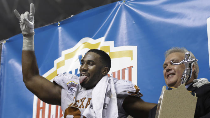 Texas' Alex Okafor, left, reacts as he receives his defensive player of the game trophy following their win over Oregon State in the Alamo Bowl NCAA football game, Saturday, Dec. 29, 2012, in San Antonio.  Texas won 31-27. (AP Photo/Eric Gay)