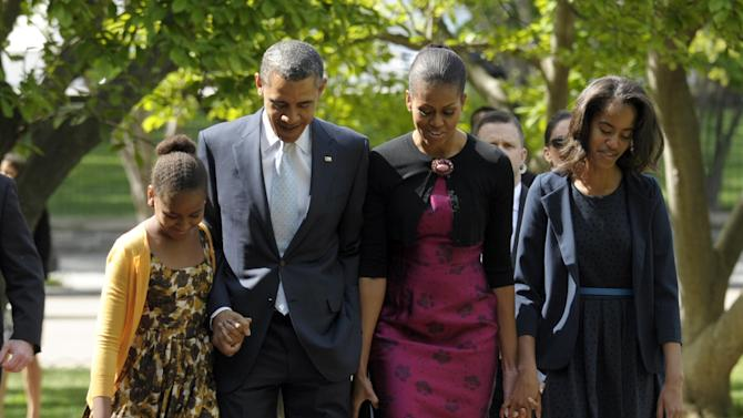 "FILE - In this April 8, 2012, file photo, President Barack Obama, first lady Michelle Obama, daughters Malia, right, and Sasha walk across the square from the White House to St. John's Episcopal Church for Easter service in Washington. Michelle Obama has a new look, both in person and online, and with the president's re-election, she has four more years as first lady, too. The first lady is trying to figure out what comes next for this self-described ""mom in chief"" who also is a champion of healthier eating, an advocate for military families, a fitness buff and the best-selling author of a book about her White House garden. For certain, she'll press ahead with her well-publicized efforts to reduce childhood obesity and rally the country around its service members. (AP Photo/Susan Walsh, File)"