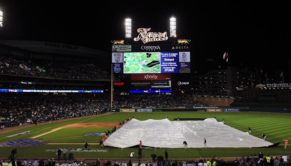 Grounds crew members cover the field during a rain delay at Game 4 of the American League championship series between the Detroit Tigers and New York Yankees Wednesday, Oct. 17, 2012, in Detroit. (AP Photo/Carlos Osorio)