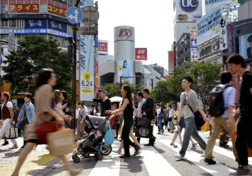 <p>Pedestrians cross a road in front of the Shibuya station in Tokyo. Sentiment among large Japanese manufacturers improved in the quarter ended June, the Bank of Japan said Monday, but confidence remained weak amid a lumbering economic recovery.</p>