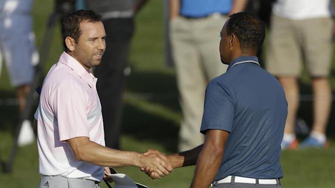 Sergio Garcia, of Spain, left, shakes hands with Tiger Woods at the conclusion of the third round of The Players championship golf tournament at TPC Sawgrass, Sunday, May 12, 2013, in Ponte Vedra Beach, Fla. Play was suspended Saturday due to darkness. (AP Photo/Gerald Herbert)