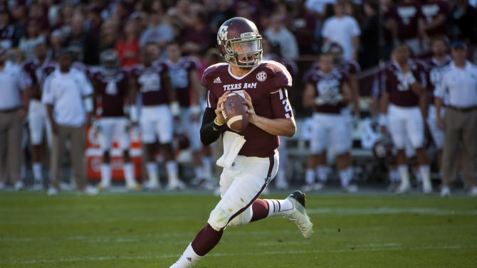 FILE - In this Nov. 17, 2012, file photo, Texas A&M's Johnny Manziel rolls out to throw a touchdown pass during the first quarter of an NCAA college football game against Sam Houston State in College Station, Texas. Manziel could become the first freshman to win the Heisman Trophy when the award is presented on Saturday night. (AP Photo/Dave Einsel, File)