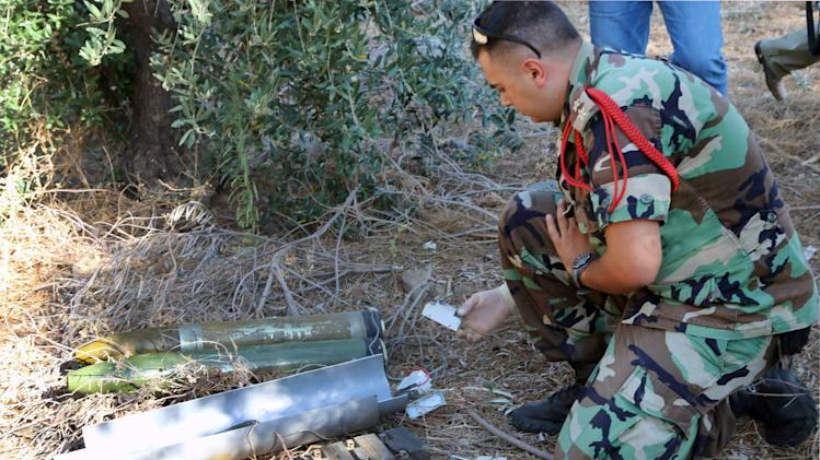 "A Lebanese army expert dismantles two rockets that were found ready to fire into northern Israel, in the southern Lebanese village of Al-Mari, Lebanon, Friday, July. 11, 2014. The Lebanese army said in a statement that an ""unknown side"" fired three rockets Friday morning from the Marjayoun-Hasbaya region toward Israel. (AP Photo/Lotfallah Daher)"