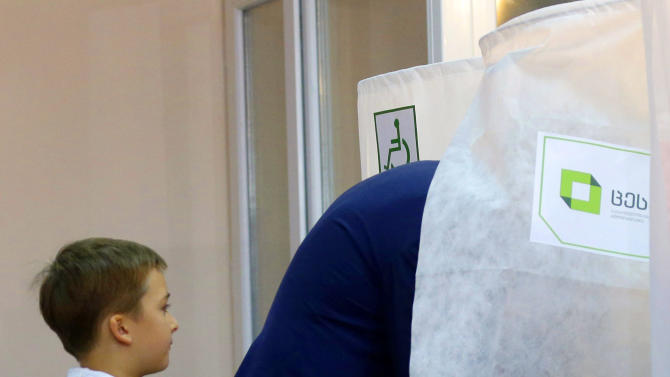 Nikoloz, left, son of Georgian President Mikhail Saakashvili, looks at his father filling in a ballot at a polling station in Tbilisi, Georgia, Monday, Oct. 1, 2012. Voters in Georgia are choosing a new parliament in a heated election Monday that will decide the future of Saakashvili's government. (AP Photo/Efrem Lukatsky)