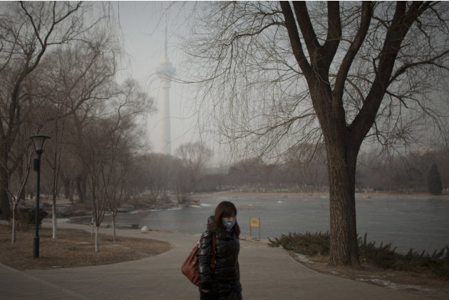 A woman wears a mask while walking in a park near the China Central Television Tower, background, on a hazy day in Beijing, China, Monday, Jan. 14, 2013. Beijing schools kept children indoors and hosp