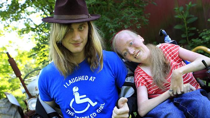 """Ally Bruener, right, poses for a photograph with friend Forest Thomer at her Alexandria, Ky. home on June 13, 2012. Thomer,  who says he was charged with disorderly conduct after using the word """"crippled"""" to promote a comedian with muscular dystrophy claims Cincinnati police violated his free speech rights, and the comedian agrees. Thomer, of Cold Spring, Ky., is to appear in a Cincinnati courtroom on the charge Wednesday. He was cited by Cincinnati police last month at a park after he and Bruener say he asked people if they wanted to """"laugh at the crippled girl.""""  (AP Photo/The Cincinnati Enquirer, Cara Owsley)  MANDATORY CREDIT;"""