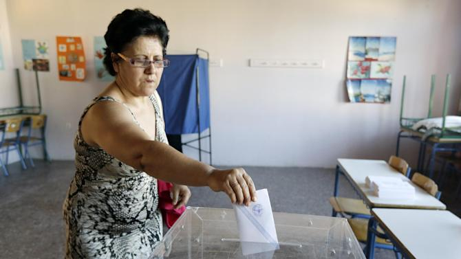 A woman casts her vote at a polling station in Athens, Sunday, July 5, 2015. Greeks began voting early Sunday in a closely-watched, closely-contested referendum, which the government pits as a choice over whether to defy the country's creditors and push for better repayment terms or essentially accept their terms, but which the opposition and many of the creditors paint as a choice between staying in the euro or leaving it. (AP Photo/Thanassis Stavrakis)